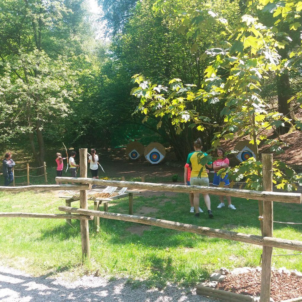 Gruppo si diverte provando il tiro con l'arco al parco avventura in Lombardia