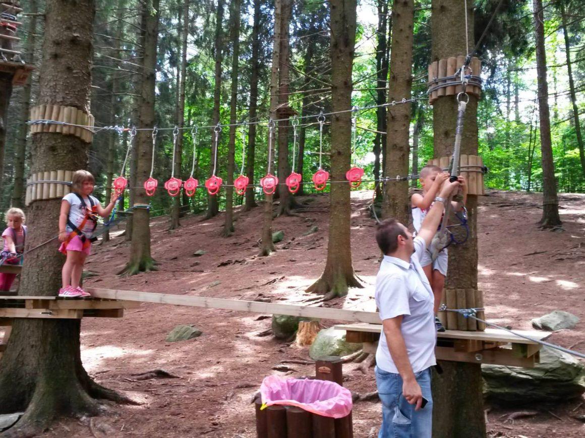 Famiglie con bambini si divertono con il percorso Bimbi del parco avventura di Civenna
