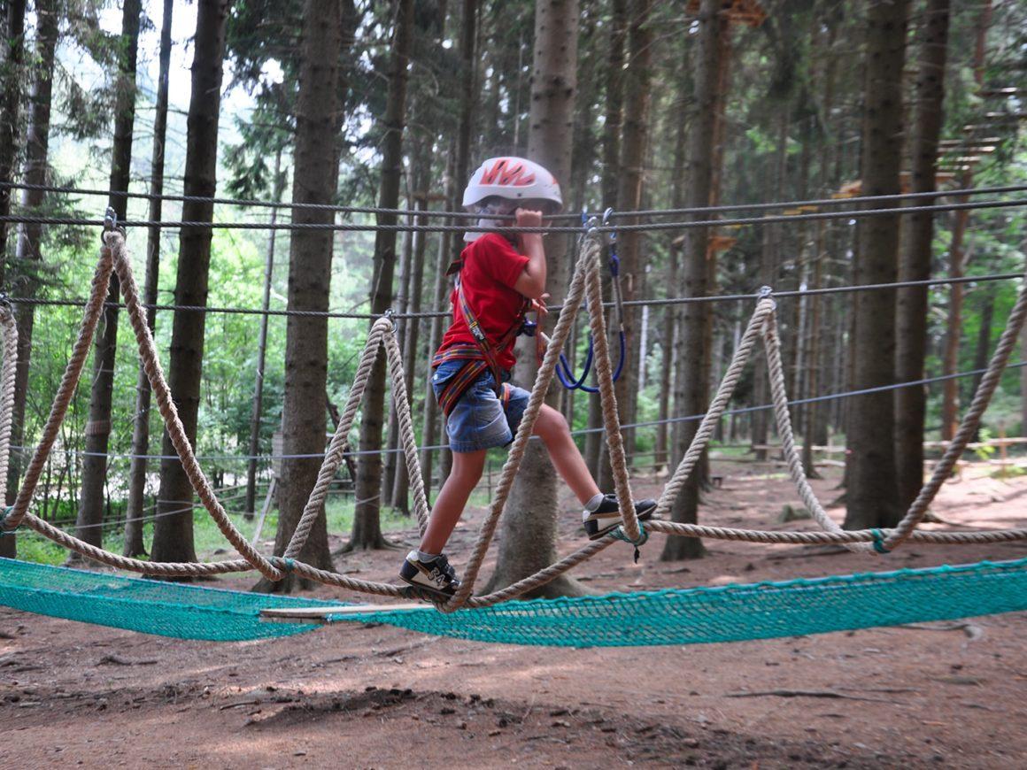Bambino supera il ponte tibetano del percorso Bimbi del parco avventura di Civenna