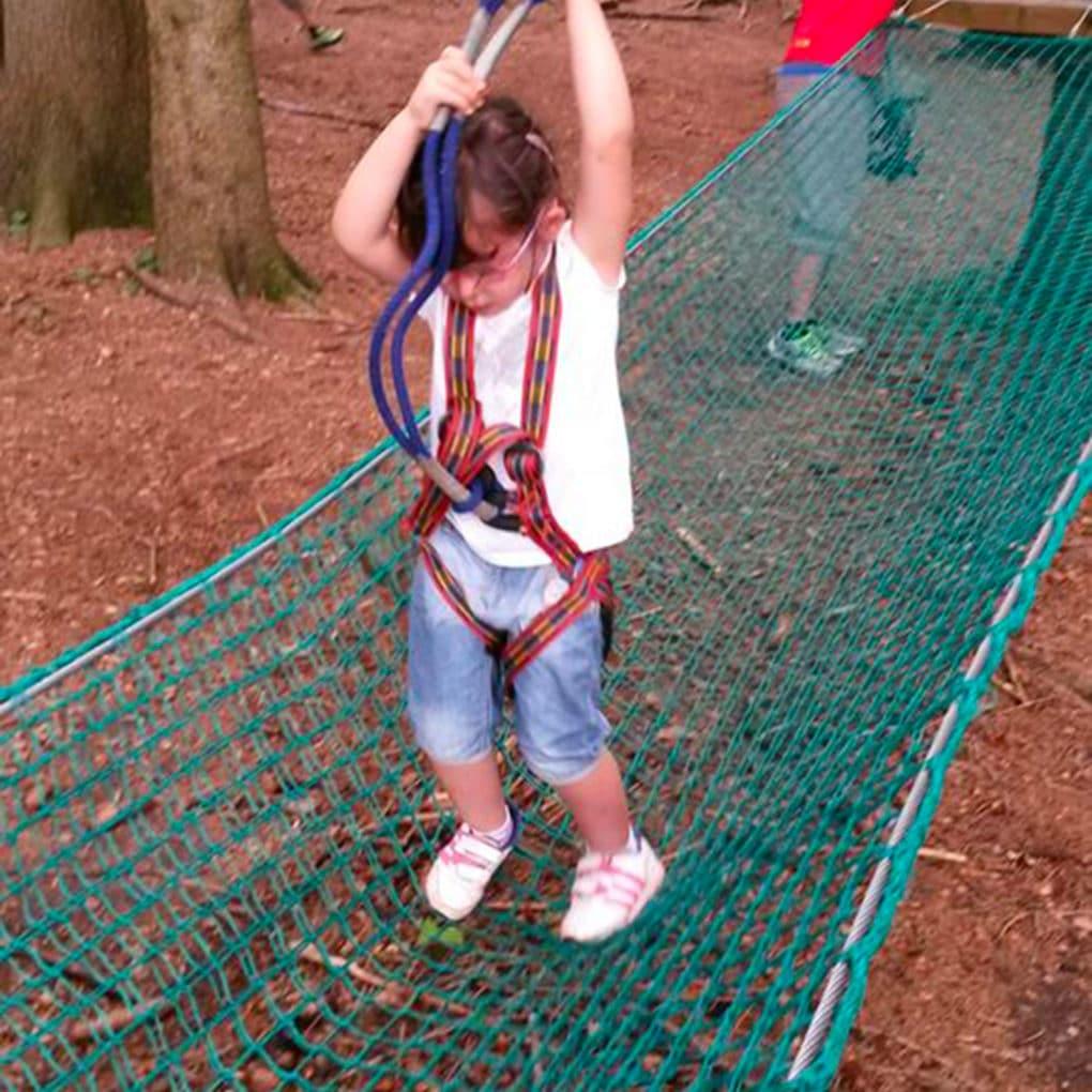 Bambina supera il ponte di rete del percorso Bimbi del parco avventura di Civenna