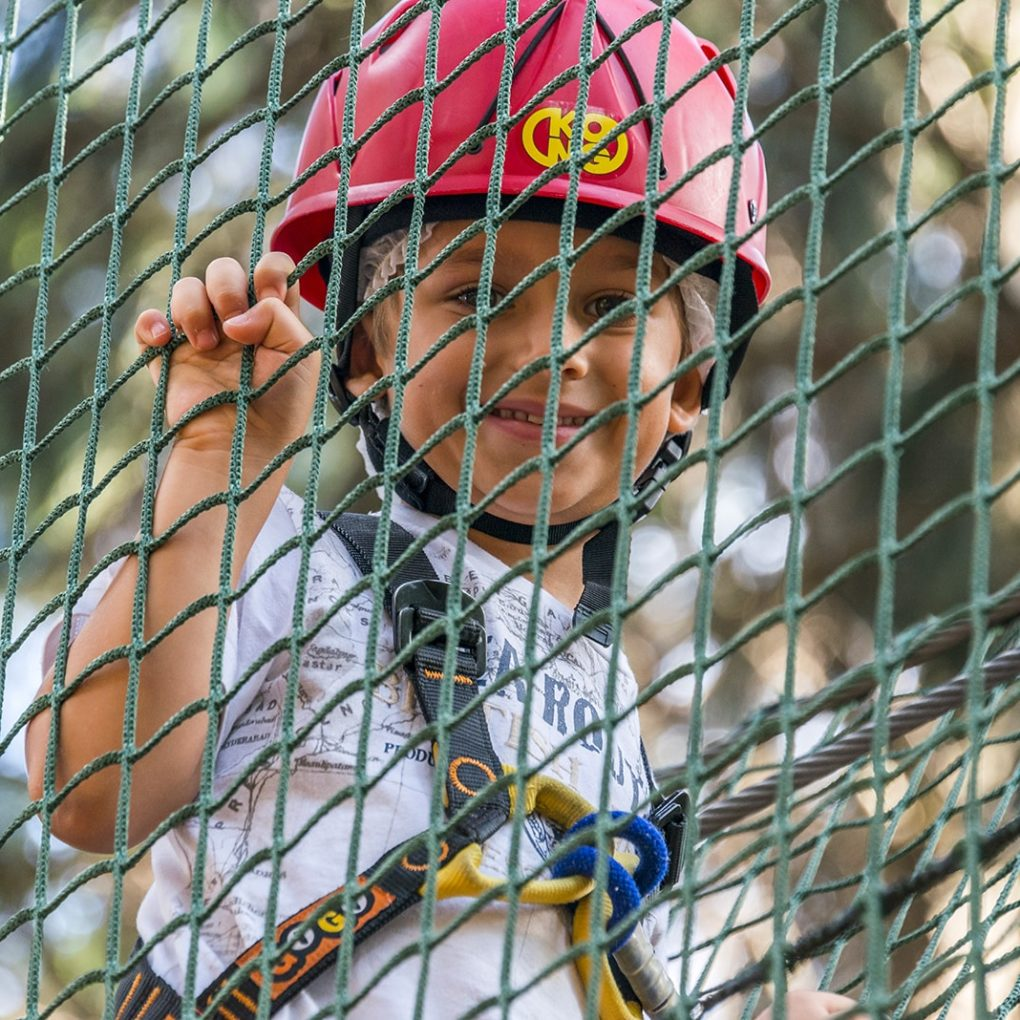 Bambino con caschetto e imbragatura di sicurezza al parco avventura vicino al lago di Como