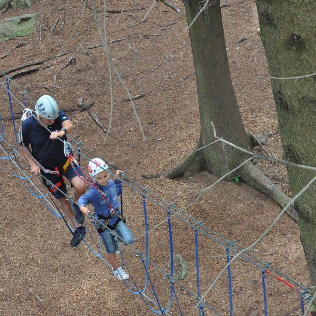 Papà e figlia superano i percorsi tra gli alberi al parco avventura in Lombardia