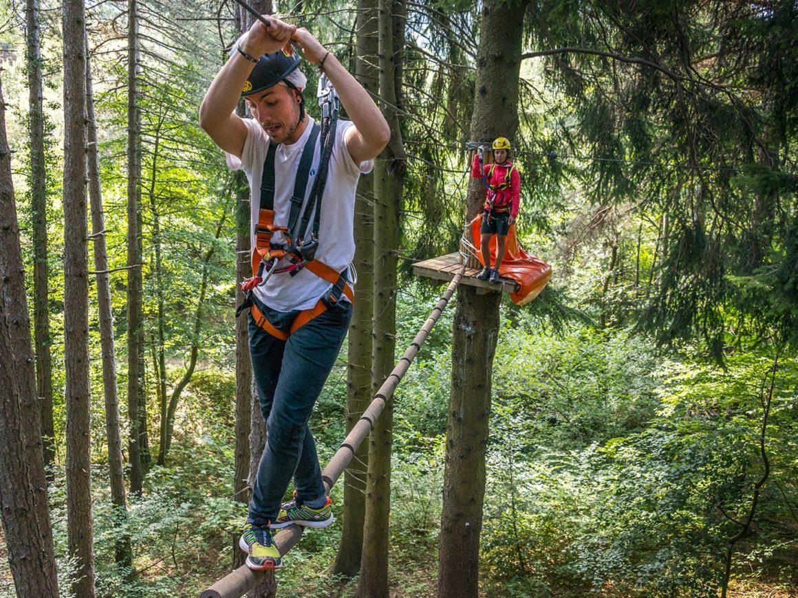 Ragazzo affronta una trave sospesa tra gli alberi nel parco avventura di Civenna