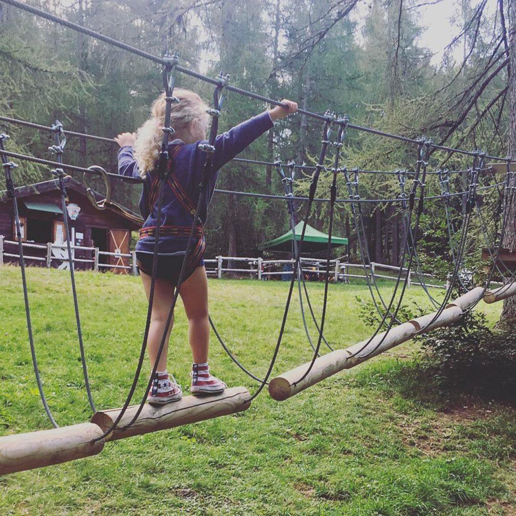 Bimba supera un ostacolo tra gli alberi nel parco avventura in Lombardia