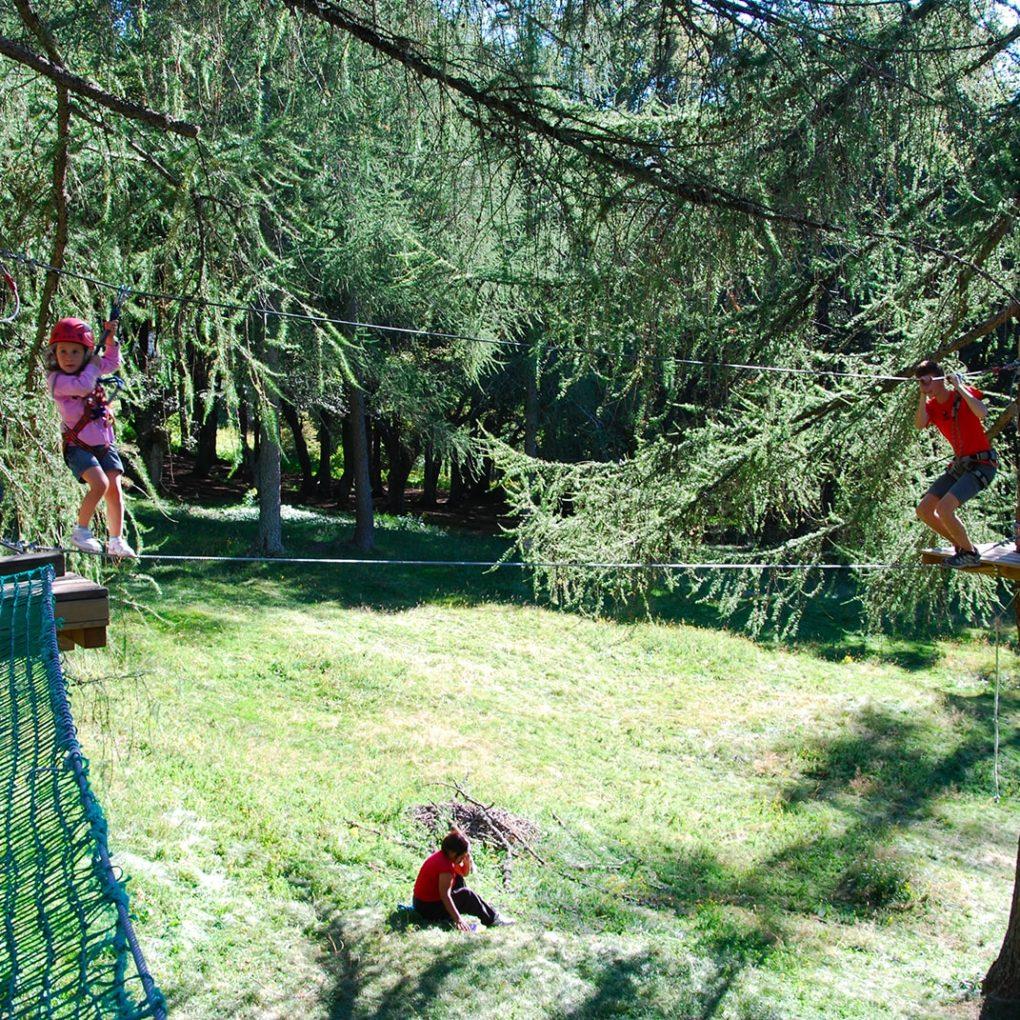 Passaggio con ponte a due corde nel percorso per famiglie del parco avventura a Margno Lancio con la teleferica del percorso per bambini