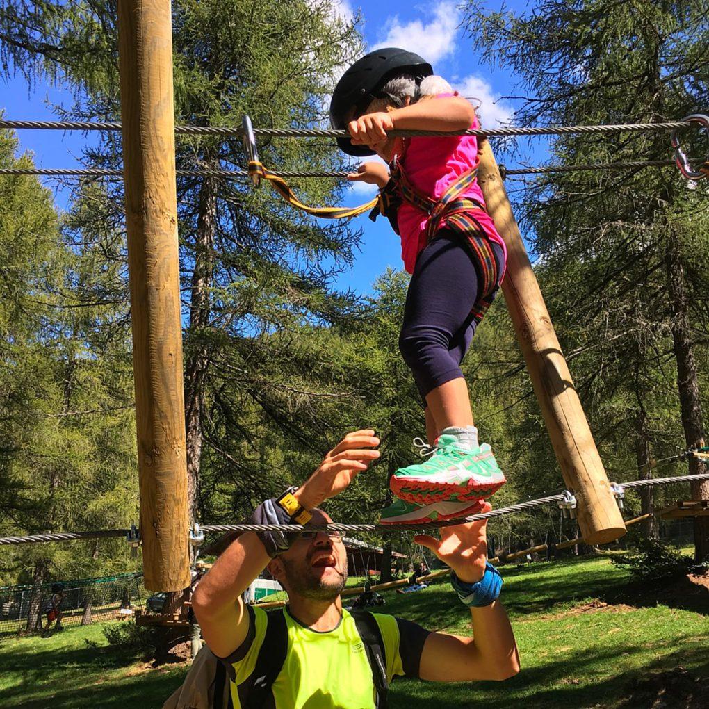 Papà segue il figlio piccolo nel percorso per i bambini nel parco divertimenti in Lombardia