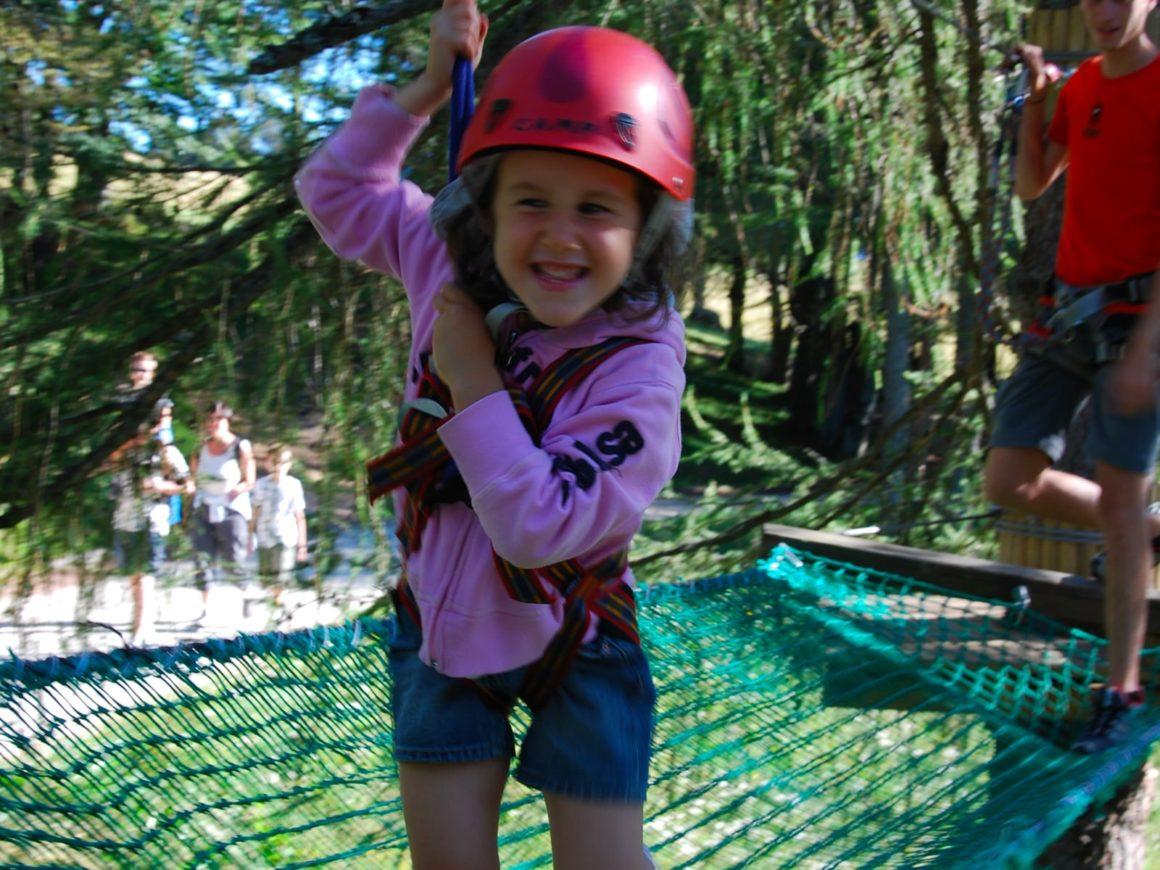 Bambina su un ponte a rete del percorso tra gli alberi nel parco avventura