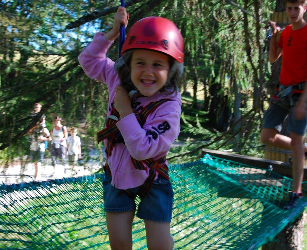 Bambino su un ponte a rete del percorso tra gli alberi nel parco avventura