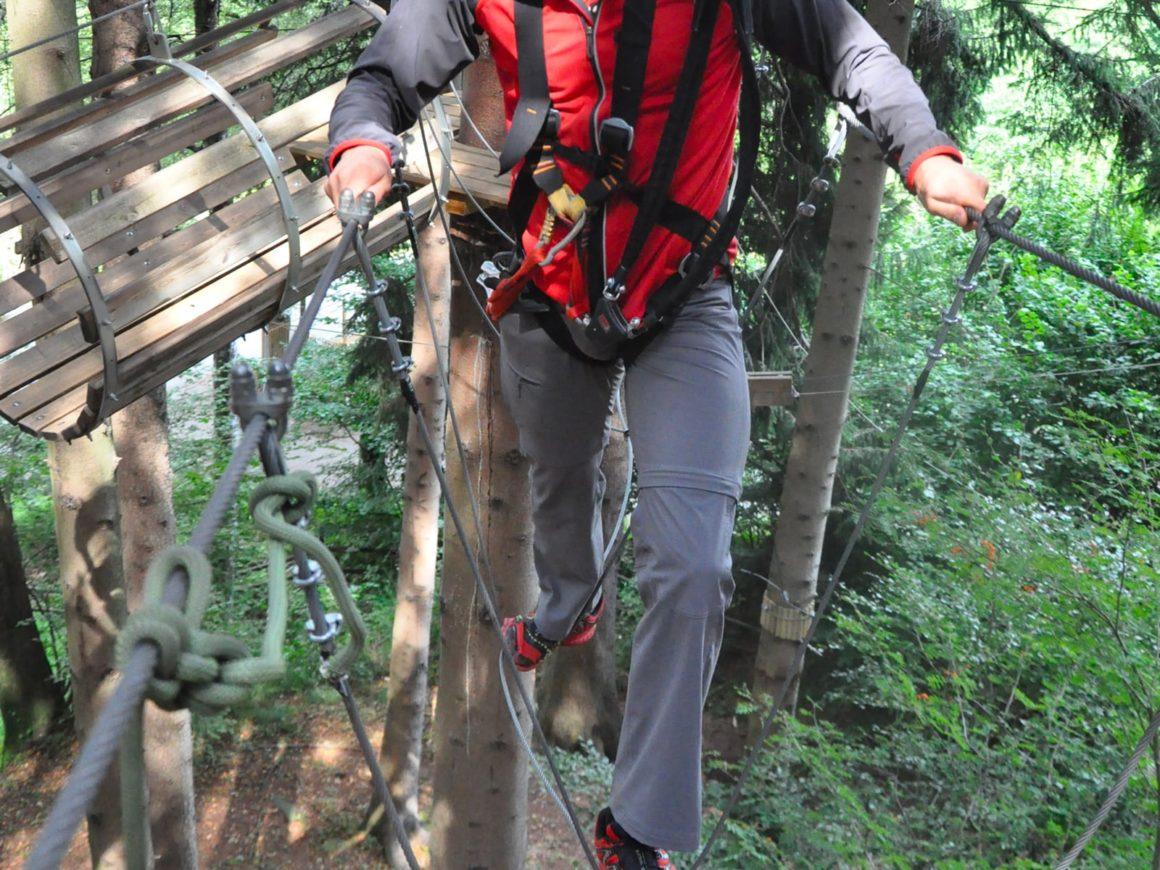 Ragazzo si diverte a superare il ponte tibetano del percorso adulti del parco divertimenti