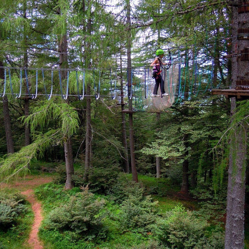 Ponte tibetano tra gli alberi del parco avventura per ragazzi e adulti