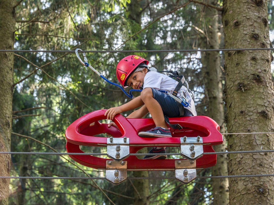 Passaggio con slittino nel percorso per bambini tra gli alberi del parco divertimenti