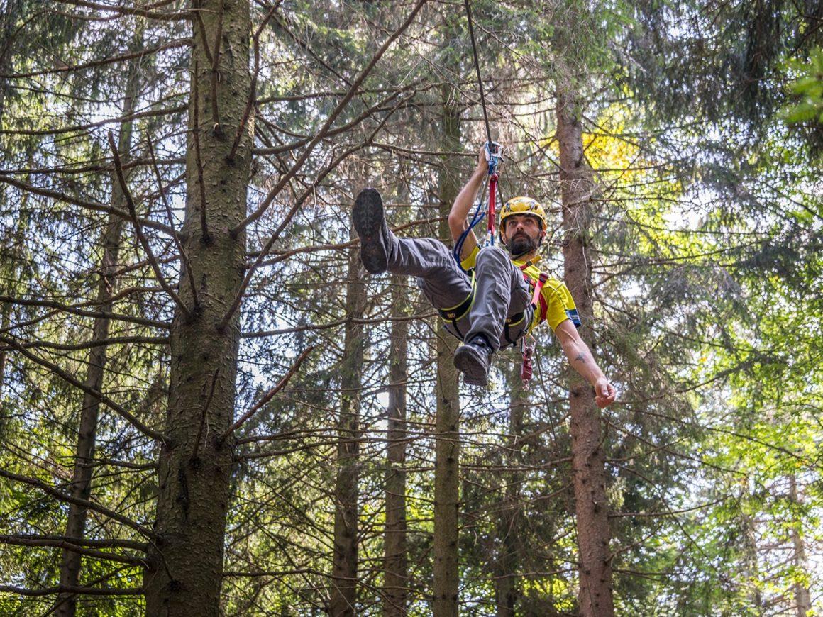 Ragazzo si diverte a saltare con la carrucola nel parco avventura di Como