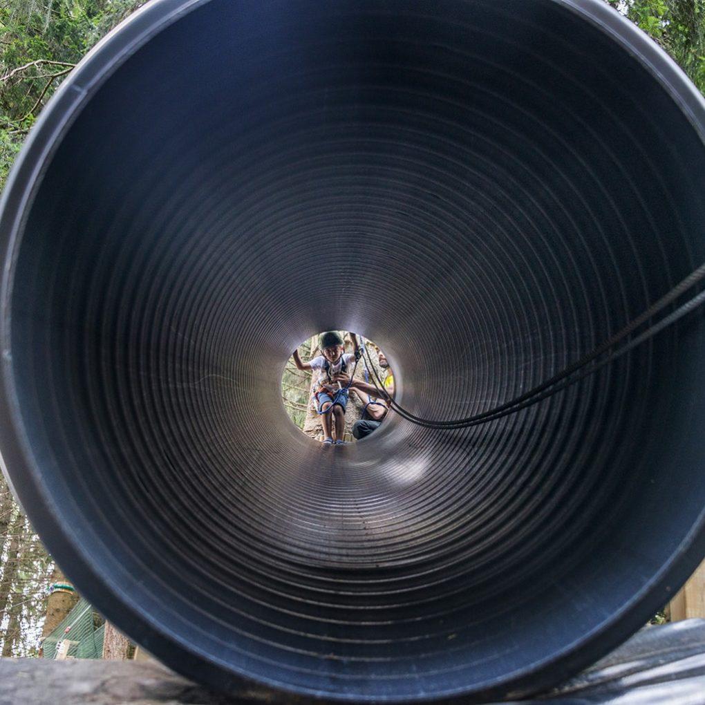 Bambino entra nel tunnel del percorso al parco divertimenti di Como