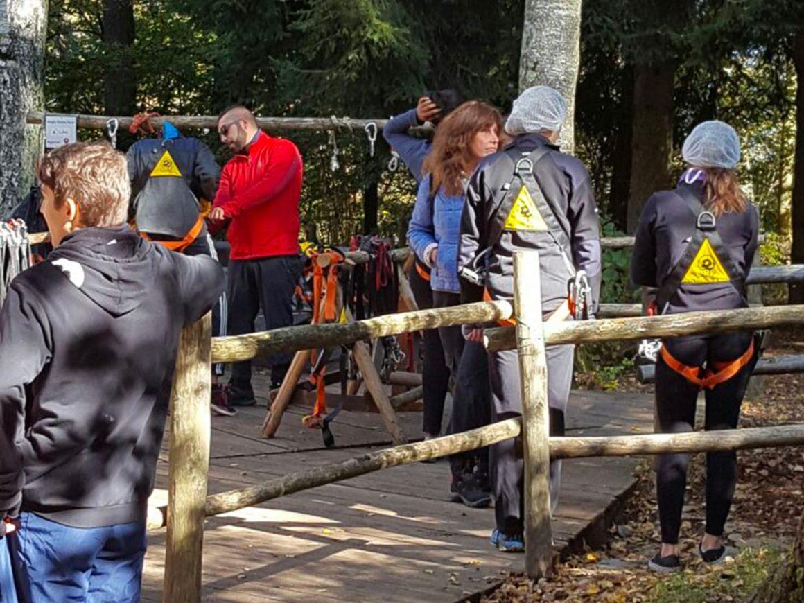 Un istruttore mostra le imbragature di sicurezza del parco avventura
