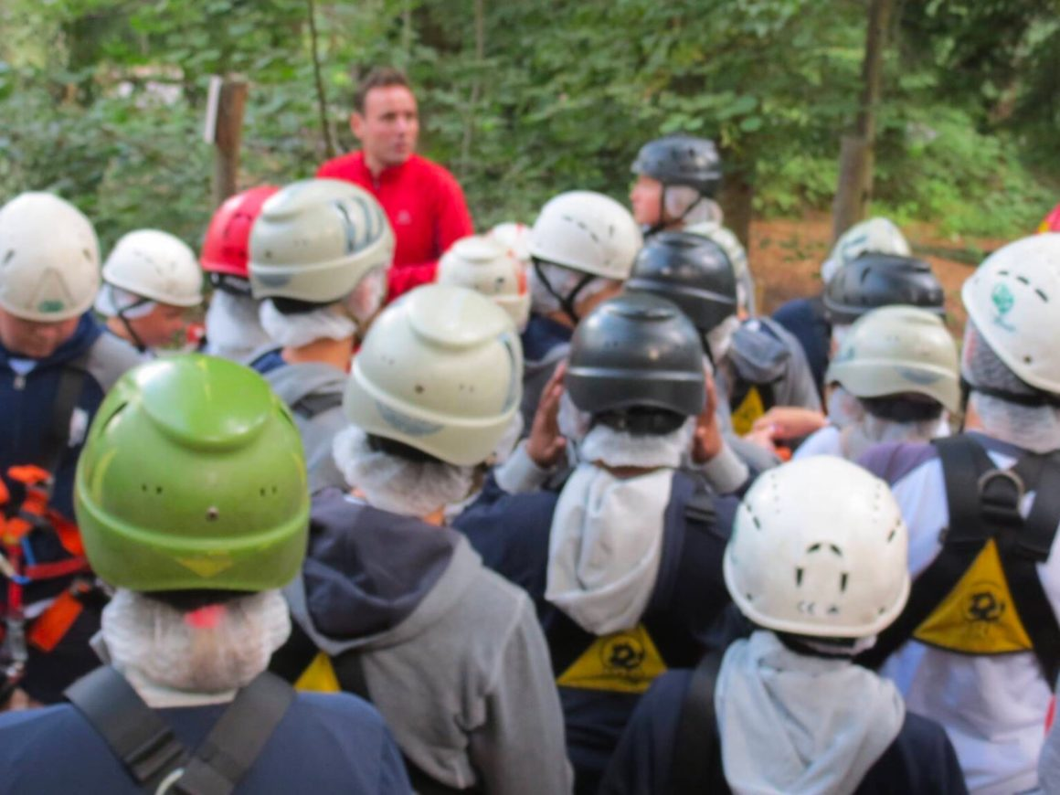 Un istruttore mostra come superare i passaggi del percorso del parco avventura Classe delle elementari ascolta le spiegazioni dell'istruttore