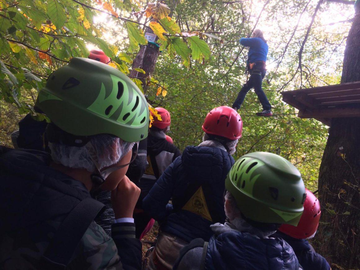 Un istruttore mostra come superare i passaggi del percorso del parco avventura
