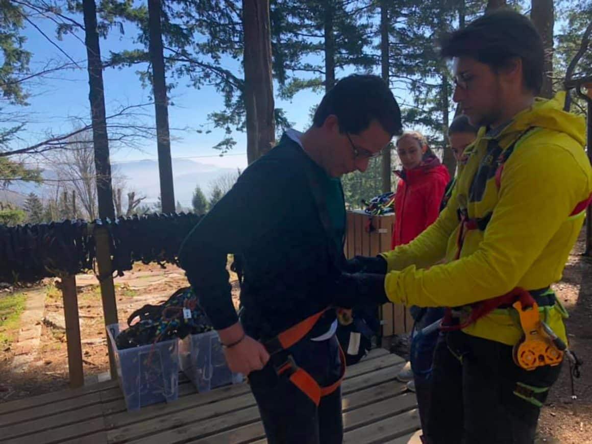 Istruttore aiuta un ospite ad indossare i dispositivi di sicurezza