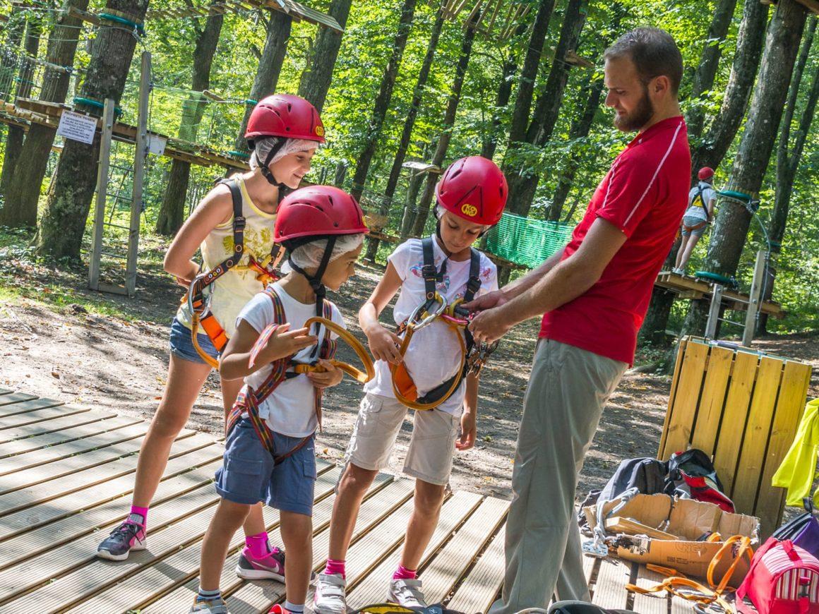 Istruttore controlla le imbracature di un gruppo di bambini